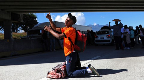 A Central American man traveling with a migrant caravan heading for the US border kneels to beg for a ride on the highway connecting Guadalajara with Tepic, Mexico, on Nov. 13, 2018. Photo: Rodingo Abd / AP