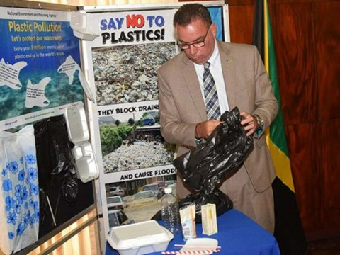 Minister without Portfolio in the Ministry of Economic Growth and Job Creation, Hon. Daryl Vaz, looks at some of the plastic products that the Government will ban starting January 2019. Photo: Jamaica Information Service